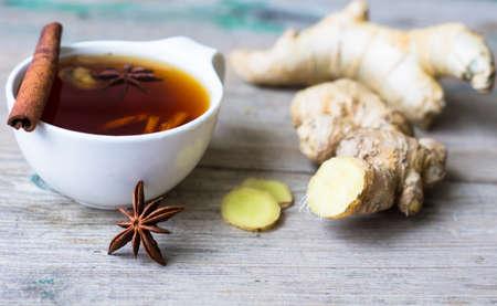 jengibre: Taza de té con jengibre, palitos de canela y anís especia estrella en el fondo rústico