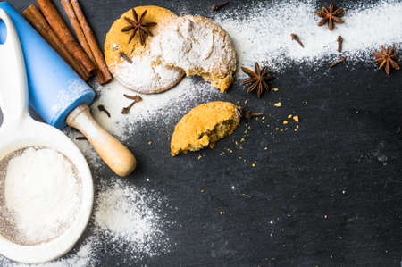 kitchen tool: Cookies bake preparing with ingredient and tools powered with flour on the black stone background Stock Photo