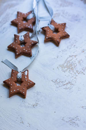 star shaped: Gingerbread cookies star shaped hanging on the ribbon over wooden background