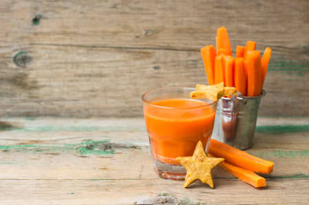 star shaped: Glass of fresh organic carrot juice, carrot sticks and star shaped carrot cookies  on the wooden background Stock Photo