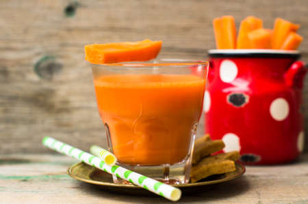 star shaped: Glass of fresh organic carrot juice, carrot sticks and star shaped carrot cookies on the wooden background