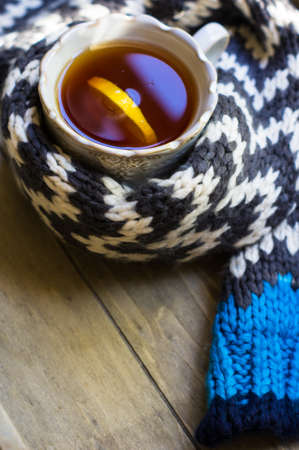 stripped: vintage cup of tea with lemon surrounded knitted stripped scarf Stock Photo