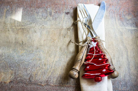 christmas food: Christmas time table setting with vintage silverware and christmas tree decorations on the rustic background