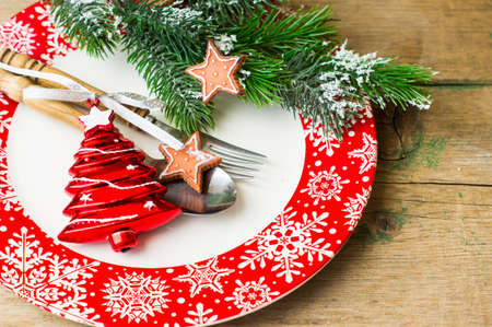 plate setting: Christmas time table setting with vintage silverware on plate and napkin. Stock Photo