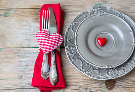 Table setting for St. Valentines day with glasses of wine, present box and red roses  in rustic style Stock Photo