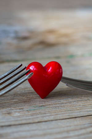 Red heart between two vintage forks on rustic wooden background