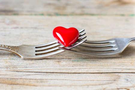 diner romantique: Coeur rouge entre deux fourchettes d'époque sur fond de bois rustique Banque d'images