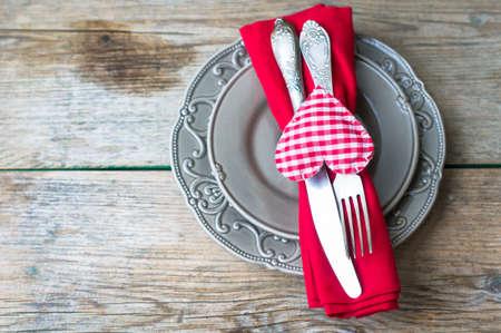 diner romantique: paramètre de table pour St. Valentines day avec des verres de vin, boîte cadeau et des roses rouges dans un style rustique