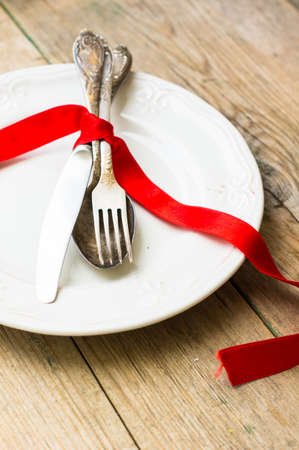 grunge flatware: Vintage silverware with red ribbn on rustic background