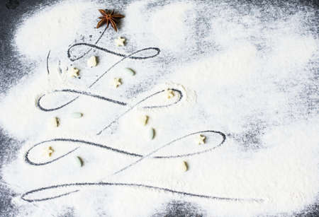 tree decorations: Christmas tree from flour on the black background with candies snd anise stars