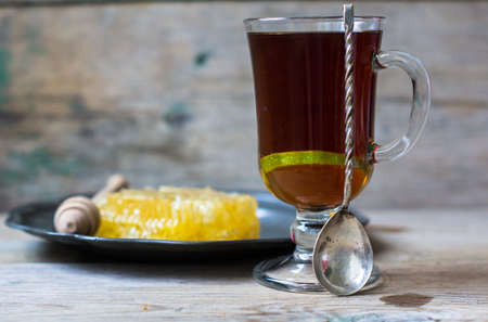 limón: Glass of tea with lemon and honey on rustic kitchen