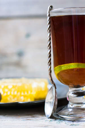 honey comb: Glass of tea with lemon and honey on rustic kitchen