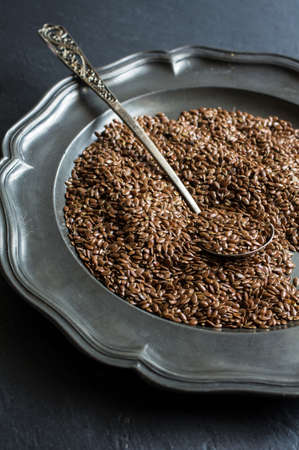 common flax: Healthy food ingredient, flax seeds and vintage silverware on black stone board
