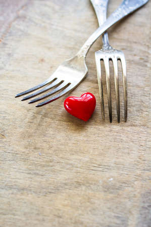 fourteenth: Red heart between two vintage forks on rustic wooden background