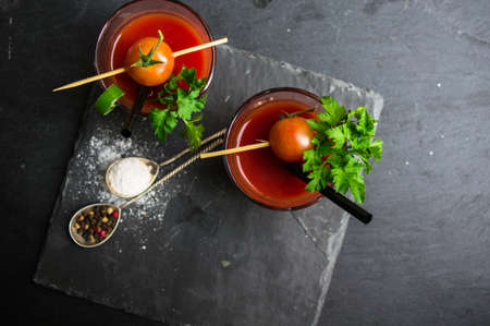 bloodymary: Fresh tomato juice with cherry tomatoes and chili pepper on rustic background Stock Photo