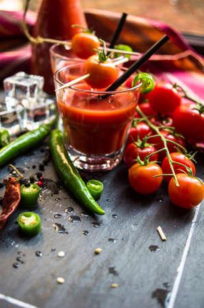 tomate cherry: Jugo de tomate fresco con tomates cherry y pimiento chile en el fondo rústico