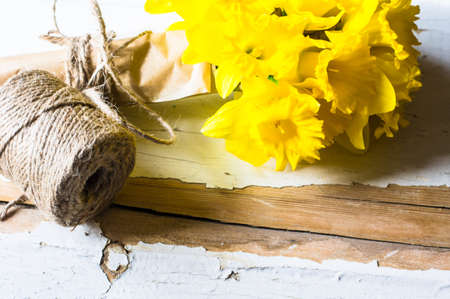 yelloow: Bright yelloow daffodil flowers in bouquet on rustic table Stock Photo