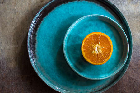 ovoid: Sliced and whole orange fruit on bright turquoise ceramic plates over rusty wooden  background