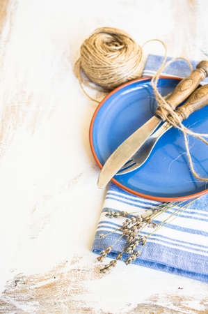 grunge cutlery: Rustic table setting with vintage silverware and bright color napkin Stock Photo