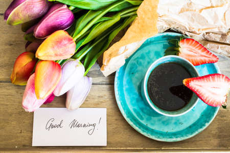 bouqet: Turquois cup of coffee, fresh strawberries and bouqet of tulips Stock Photo