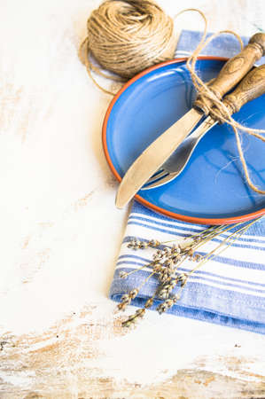 grunge silverware: Rustic table setting with vintage silverware and bright color napkin Stock Photo