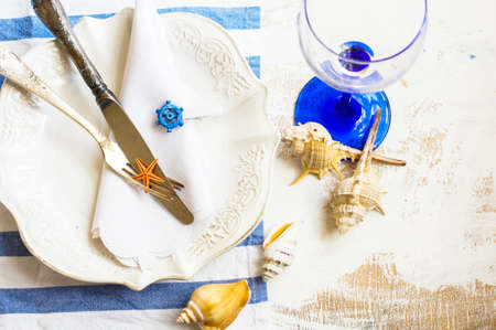 sea star: Marine table setting with vintage plate, silverware, napkin, wine glass and sea star in blue tones. Stock Photo