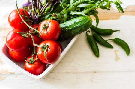 peper: Fresh organic vegetables like a tomatoes, cucumer, green peper,  spinach and parsley on rustic wooden background Stock Photo