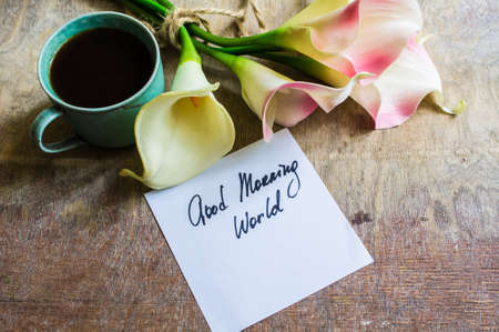 Cup of coffee and calla lily flowers on rustic background