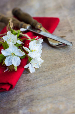 blossom time: Spring time table setting with cherry blossom and vintage silverware on rustic background Stock Photo