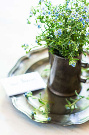 lowers: Vintage table setting with forget-me-not lowers on rustic interior