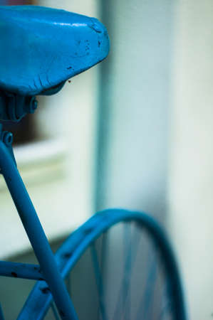 old fashioned sepia: seat and wheel of vintage blue bicycle on the street