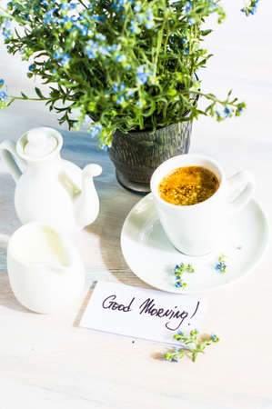 drink me: Forget-me-not spring flowers and cup of coffee  on wooden rustic background Stock Photo