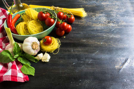 italy background: Pasta cooking concept with  basil, tomatoes,  pepper chili, garlic and pasta on vintage wooden background