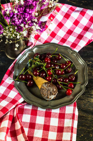 wildberry: Wild flowers and fresh organic cherries with ice cream on vintage plate Stock Photo