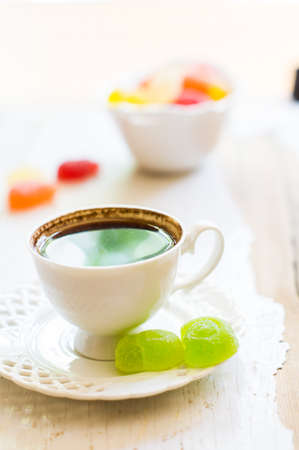 marmelade: Cup of coffee with marmelade sweets on rustic table Stock Photo