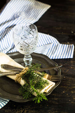 old styled: Rustic table setting with vintage silverware ad plates on old styled napkins