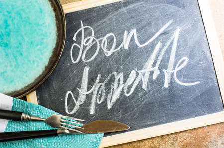bon: Bon appetite on a chalkboard with rustic silverware and napkin Stock Photo