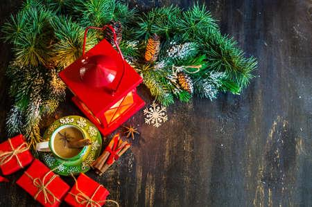 encendedores: tiempo de Navidad latern rojo con luz de velas, regalos y una taza de café con leche con especias como el anís estrellado y ramas de canela