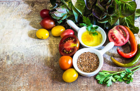 Ingredients for summer salad - romano salad, tomatoes, parsley, flax seeds and oil. Stock Photo
