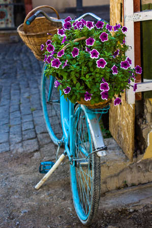 Blue vintage bicycle with bright flowers on the street of Old Tbilisi, Georgia
