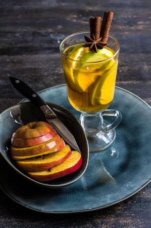 Apple cider with cinnamon sticks and fresh organic apples on dark wooden background