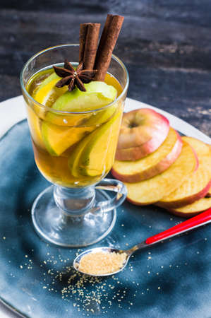 Apple cider with cinnamon sticks and fresh organic apples on dark wooden background