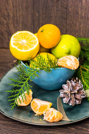 chritmas: Fresh organic lemons and Chritmas tree decorations on dark wooden table