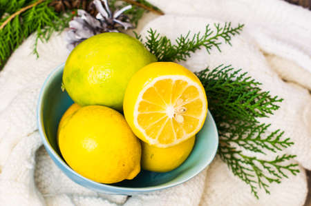 Fresh organic lemons and Chritmas tree decorations on dark wooden table