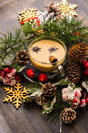 Cup of coffee with milk and spices on decorated for Christmas dark background