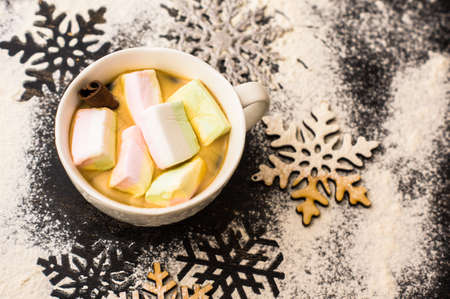Christmas or New Year composition with hot chocolate and marshmallows, decorated with fir cones and holiday balls and jingle bells on  dark vintage wooden background,