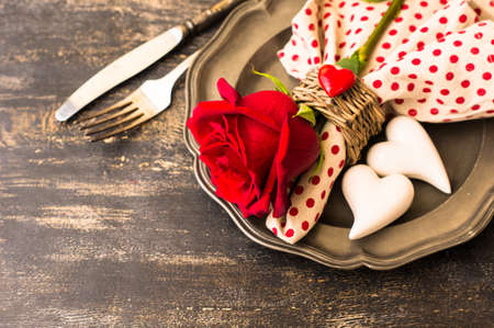 romantic places: Festive table seting with red rose and heart on dark rustic table with copyspace