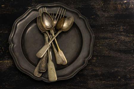 grunge cutlery: Vintage plate full of vintage silverware on rustic wooden table Stock Photo