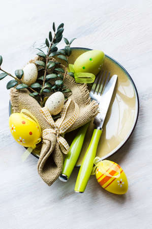 Table setting for Easter dinner with tulips and eggs on rustic wooden table
