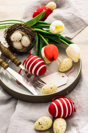 Table setting for Easter dinner with tulips and eggs on white wooden table Imagens